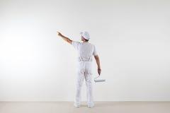 Retrovisione dell'uomo del pittore che indica con il dito la parete in bianco, wi fotografia stock libera da diritti