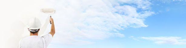 Retrovisione dell'uomo del pittore con il rullo di pittura che dipinge il cielo blu immagine stock libera da diritti