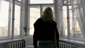 Retrovisione della bionda in cardigan nero sulle sue spalle che si muovono lentamente verso la finestra a casa nella stanza lumin archivi video