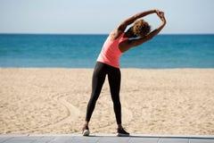 Retrovisione della donna americana che fa allungando esercizio alla spiaggia Immagini Stock