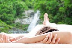 Retrovisione della donna asiatica che si rilassa su un sofà alla cascata Fotografia Stock
