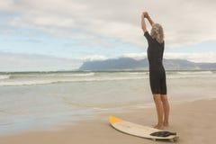 Retrovisione della donna che allunga mentre facendo una pausa surf contro il cielo nuvoloso Fotografie Stock Libere da Diritti