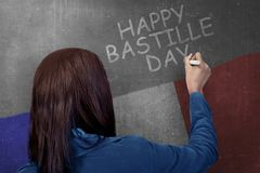Retrovisione della donna che scrive giorno di Bastille felice sulla parete immagini stock libere da diritti