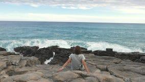 Retrovisione della donna che si siede sul litorale roccioso e che esamina oceano d'ondeggiamento defocused nei precedenti Colori  stock footage