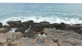 Retrovisione della donna che si siede sul litorale roccioso e che esamina oceano d'ondeggiamento defocused nei precedenti Colori  video d archivio