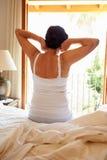 Retrovisione della donna che sveglia a letto nella mattina Fotografia Stock Libera da Diritti