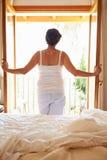 Retrovisione della donna che sveglia a letto nella mattina fotografie stock libere da diritti