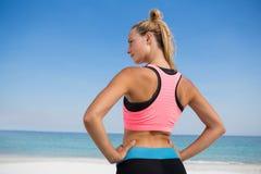 Retrovisione della donna con la mano sull'anca alla spiaggia Fotografia Stock