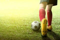 Retrovisione della donna del giocatore di football americano in jersey arancio che dà dei calci alla palla immagini stock libere da diritti