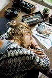Retrovisione della donna dell'artista che prende un pelo sulla tavola di lavoro Fotografia Stock Libera da Diritti