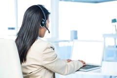 Retrovisione della donna di affari con la cuffia avricolare facendo uso del computer portatile Immagine Stock