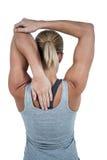 Retrovisione della donna muscolare che allunga il suo braccio Immagine Stock