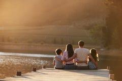 Retrovisione della famiglia che sta sul molo di legno dal lago immagini stock