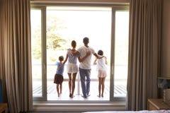 Retrovisione della famiglia sul balcone che guarda fuori il nuovo giorno immagini stock