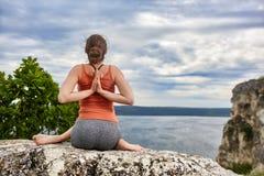 Retrovisione della giovane donna nella posa di yoga che si siede sulla roccia sopra il fiume Immagine Stock