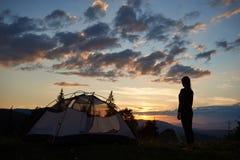Retrovisione della giovane signora che sta sopra il campeggio vicino della montagna all'alba che gode della vista fotografie stock libere da diritti