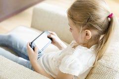 Retrovisione della ragazza che gioca video gioco tenuto in mano a casa fotografia stock