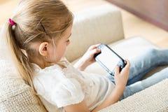 Retrovisione della ragazza che gioca video gioco tenuto in mano a casa fotografie stock