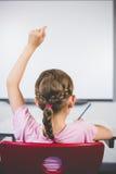Retrovisione della scolara che solleva la sua mano in aula Immagini Stock Libere da Diritti