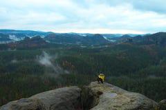 Retrovisione della viandante alta in rivestimento nero giallo sul picco roccioso mentre godendo di una valle di cui sopra delle m Immagine Stock