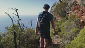 Retrovisione della viandante che cammina sulla scogliera contro il mare video d archivio