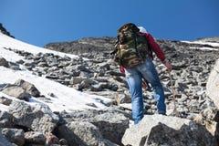 Retrovisione della viandante che scala sul pendio pietroso ripido in montagne fotografia stock libera da diritti
