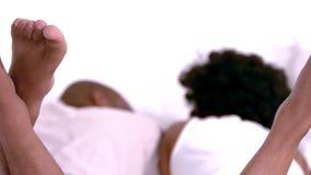 Retrovisione delle coppie che oscillano il loro piede stock footage