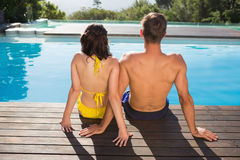 Retrovisione delle coppie che si siedono dalla piscina Fotografia Stock Libera da Diritti