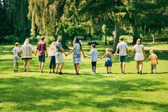Retrovisione delle coppie felici che camminano con i bambini Fotografia Stock Libera da Diritti