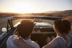 Retrovisione delle coppie sul viaggio stradale che conduce automobile convertibile classica verso il tramonto immagine stock