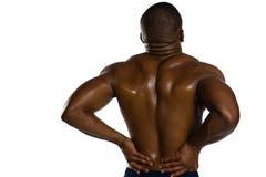 Retrovisione dello sportivo senza camicia che soffre dal dolore alla schiena Fotografia Stock