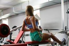 Retrovisione di addestramento dell'atleta femminile sul simulatore fotografia stock