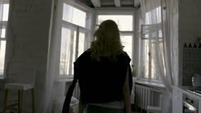 Retrovisione di bella bionda esile a casa dalla finestra azione Punto di vista posteriore di una ragazza con il cardigan nero su  archivi video