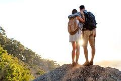 Retrovisione di escursione delle coppie con lo zaino che sta insieme sulla cima della collina che gode di bello paesaggio Uomo e  fotografia stock libera da diritti