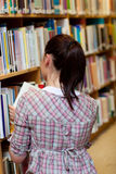 Retrovisione di giovane donna che cerca un libro Fotografia Stock Libera da Diritti