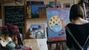 Retrovisione di giovane ragazza del pittore nell'immagine di natura morta della pittura del grembiule su tela in classe arte Immagini Stock