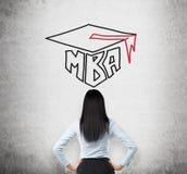 Retrovisione di giovane signora castana che sta pensando al grado di MBA Immagine Stock Libera da Diritti
