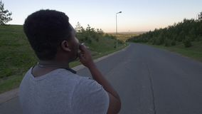 Retrovisione di giovane uomo afroamericano che cammina giù la strada vuota e la sigaretta di fumo al tramonto video d archivio