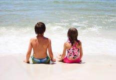 Retrovisione di piccoli bambini che si siedono sulla spiaggia Immagini Stock Libere da Diritti