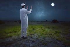 Retrovisione di pregare musulmano asiatico dell'uomo Immagini Stock