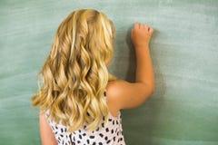 Retrovisione di scrittura della ragazza della scuola sulla lavagna in aula Immagine Stock Libera da Diritti