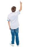 Retrovisione di un ragazzo di banco che indica verso l'alto fotografia stock