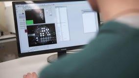 Retrovisione di un redattore di foto maschio casuale facendo uso del computer in un ufficio luminoso Retrovisione del giovane che stock footage