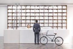Retrovisione di un uomo in una biblioteca Immagini Stock
