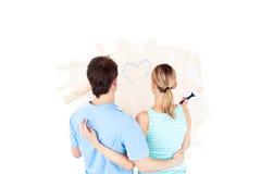 Retrovisione di una coppia che esamina una pittura del cuore Fotografie Stock