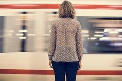 Retrovisione di una donna bionda che aspetta al binario del treno immagine stock