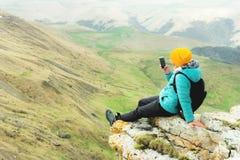 Retrovisione di una donna che si siede su una roccia in vestiti di inverno e che porta un cappello su uno smartphone Montagne di  fotografia stock