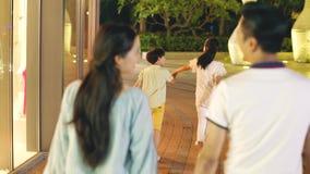 Retrovisione di una famiglia asiatica di 4 che cammina ad una zona commerciale alla notte stock footage