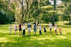 Retrovisione di una famiglia felice di undici che cammina Fotografie Stock