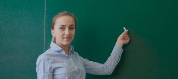 Retrovisione di uno studente o di un insegnante con scrittura castana lunga dei capelli su una lavagna o su una lavagna verde in  Immagine Stock